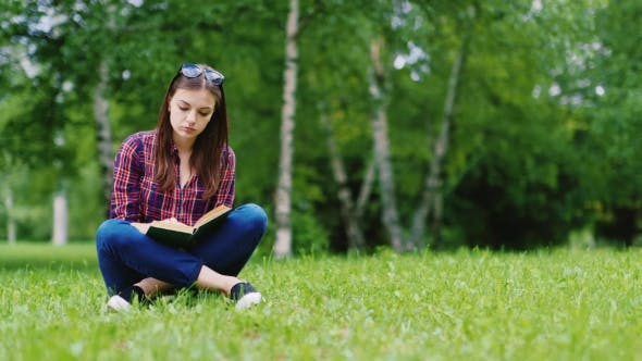 Thumbnail for Pretty Young Woman Reading a Book In The Park. He Sits On The Green Grass
