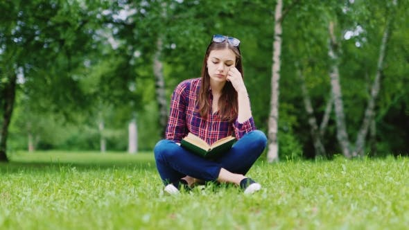 Cover Image for Young Student Reading a Book In The Park