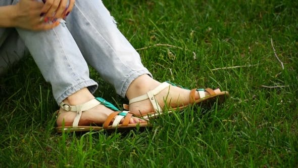 Thumbnail for Caucasian Young Woman Sitting On The Grass In The Park Buttons Their Sandals. Footage Girl Relaxing