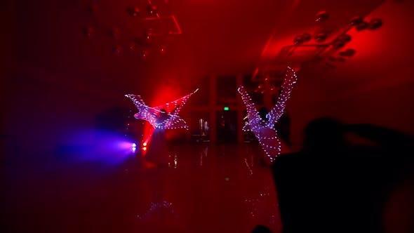 Die Mädchen führen einen Tanz mit LED-Flügeln auf. LED-Lichter und bunter Hintergrund leuchten im Dunkeln. Young