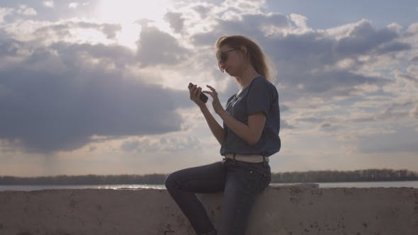 Thumbnail for Girl Dressed In Denim And Sunglasses Is Sitting On Quay And Using Phone