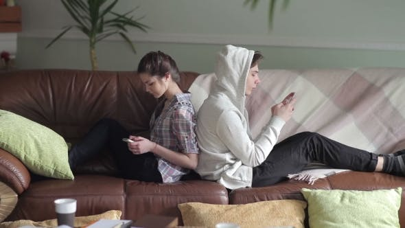 Cover Image for Couple Sits Back To Back On The Couch With Phones.