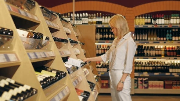 Thumbnail for Young Beautiful Woman Chooses Wine In The Supermarket.