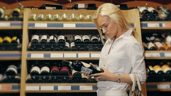 Cover Image for Young Beautiful Woman Chooses Wine In The Supermarket.