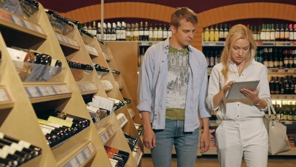 Thumbnail for Young Couple In The Store Checking List Of Products On Tablet PC And Taking Two Bottles Of Wine