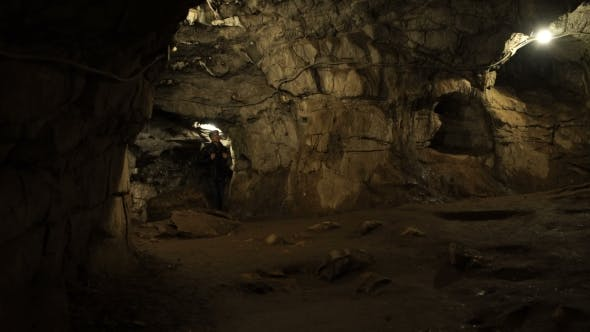 Thumbnail for A Young Man Is Standing Inside a Rock Cave