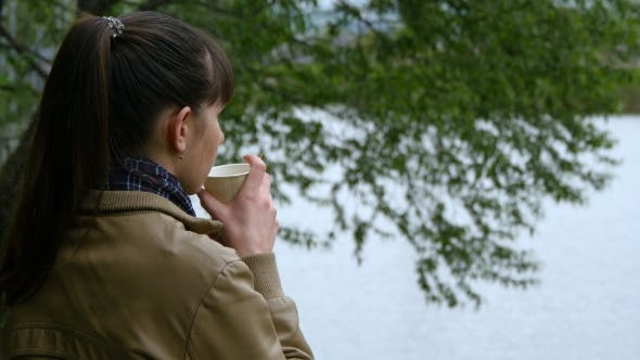 Thumbnail for Beautiful Young Girl Stands On The Embankment Of The River And Drinking Cup Of Takeaway Coffee