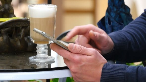 Thumbnail for Male Hands Using Smartphone and Having Cappuccino at Cafe in Shopping Mall.