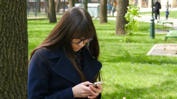 Thumbnail for Beautiful Woman In Glasses Uses Cell Smartphone Outdoors In The Park  - Detail . Young Attractive