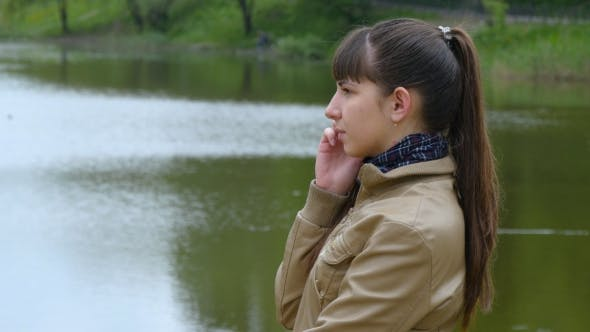Thumbnail for Young Woman Stands On The Embankment Of The River And Talking On a Cell Phone