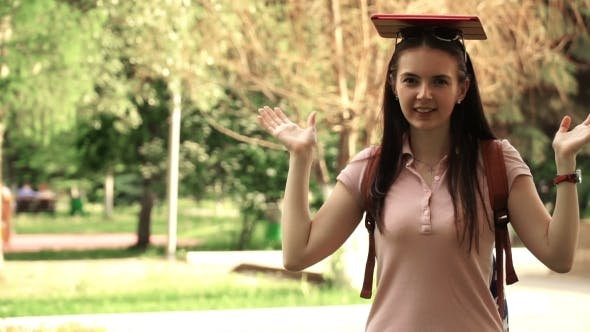 Thumbnail for Footage Young Beautiful Woman Walking In The Park. Girl Put The Tablet On His Head.