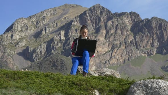 Thumbnail for Young Girl With Laptop On The Background Of Formidable Cliffs