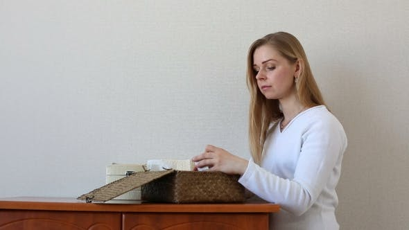 Thumbnail for Beautiful Blonde Woman Looking For Something In Jewelry Boxes Standing Near a Chest Of Drawers