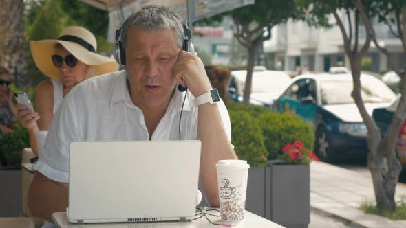 Man Wearing Headset Video Chatting In Outdoor Cafe