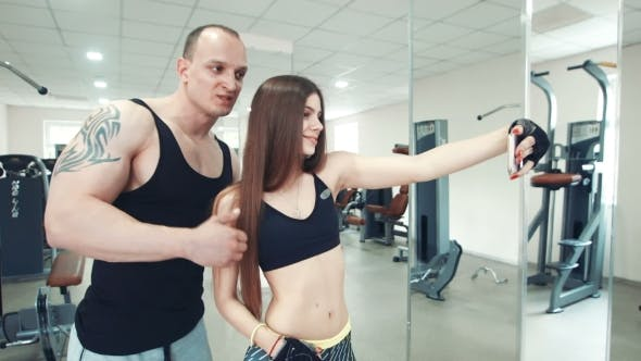 Thumbnail for Long-haired Sportswoman And Tattooed Sportsman Taking Selfie In Gym