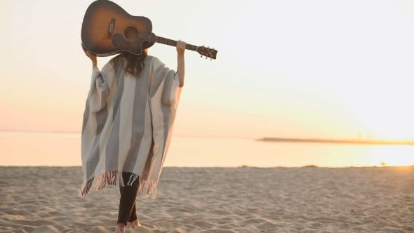 Thumbnail for Woman Back Walking On The Beach With Guitar