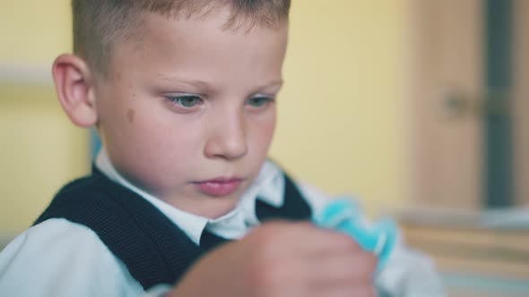 Thumbnail for Kid Plays with Turning Spinner Resting at Break in Classroom