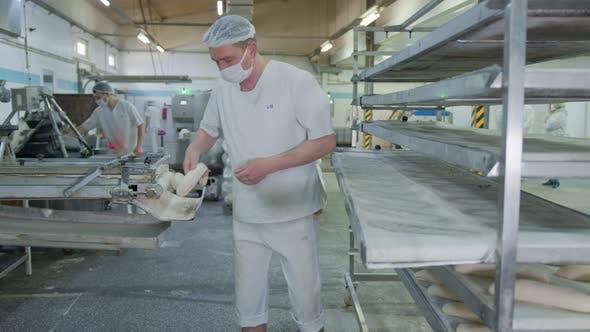 Thumbnail for Bäckerei Backen Bäckerei. Der Mitarbeiter der Bäckerei verbreitet die aus dem Teig hergestellten Backwaren