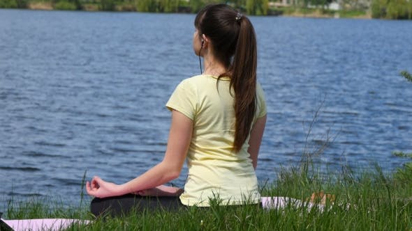 Young girl meditating and listening music on headphones