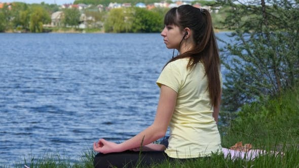Thumbnail for Young Woman Meditating And Listening Music On Smartphone In Headphones In Lotus Position