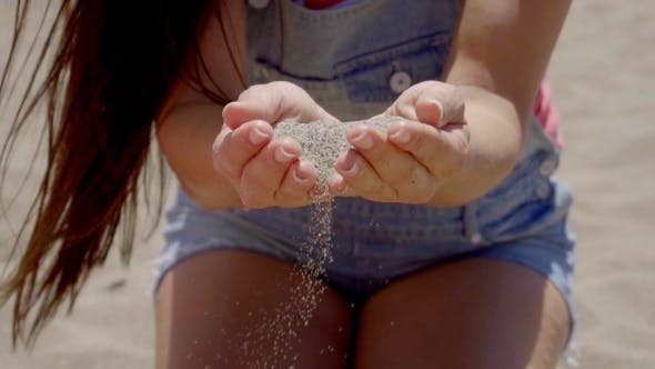 Thumbnail for Sand Falling Through Hands Of Woman In Shorts