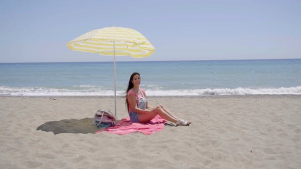 Thumbnail for Lone Woman Sitting On Beach Under Umbrella