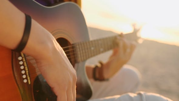 Thumbnail for Young Boy Plays Guitar at Sunset