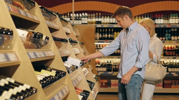 Thumbnail for Young Beautiful Couple Choose Wine In The Supermarket