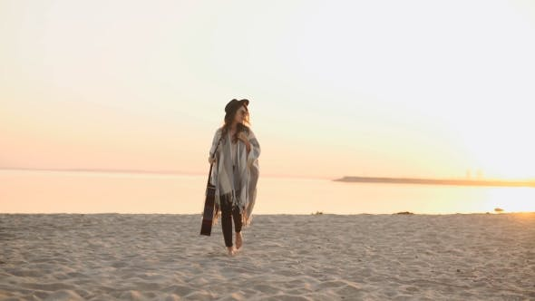 Cover Image for Woman Back Walking On The Beach With Guitar