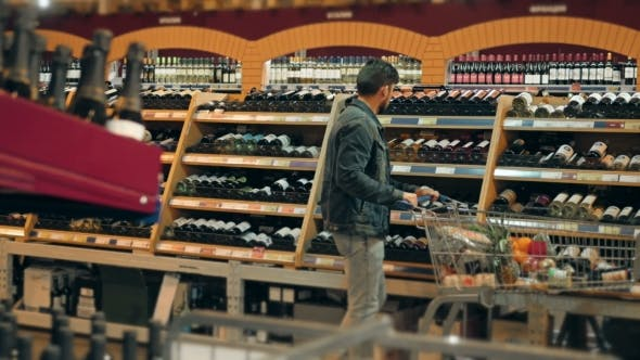 Thumbnail for Young Man Chooses Bottle Of Wine In The Supermarket