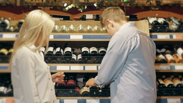 Cover Image for Couple Choose Wine Using Cellphone In Supermarket