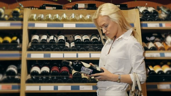Thumbnail for Beautiful Woman Chooses Wine In The Supermarket.