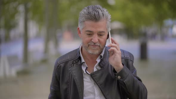 Thumbnail for Happy Mature Man Talking By Smartphone Outdoor