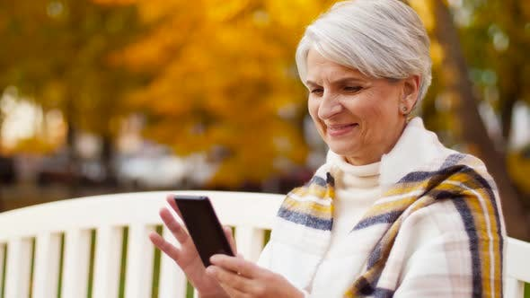 Cover Image for Happy Senior Woman with Smartphone at Autumn Park 35