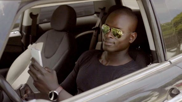 Thumbnail for Handsome Black Man Seated In Car With Phone
