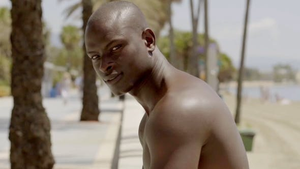 Shirtless Muscular Black Man Near Sandy Beach