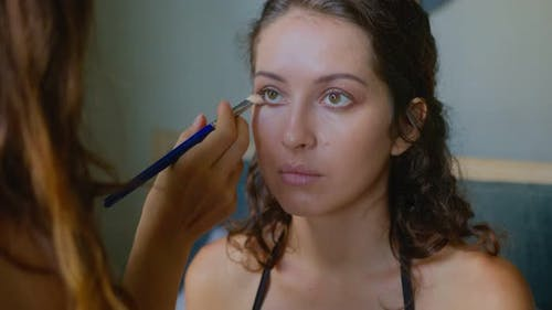 A Makeup Artist Makes a Bright Makeup for a Beautiful Girl Model