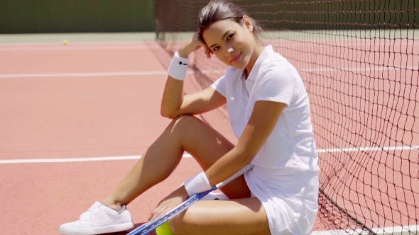 Thumbnail for Smiling Woman With Racket Sitting On Tennis Court