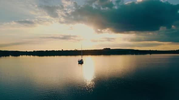 Luftaufnahme Eine Yacht bei Sonnenuntergang in der Nähe des Binnenschiffs. Flug bei Sonnenuntergang In der Nähe der Yacht mit einem Segel. Die Sonne