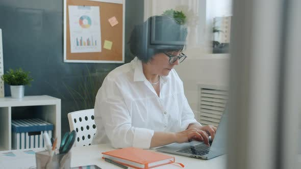 Serious Business Lady Using Laptop Typing Concentrated on Corporate Work in Office