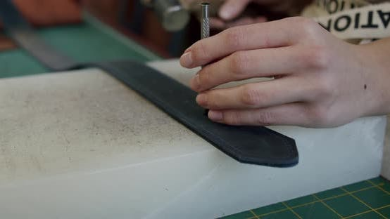 Close Up Shot of Specialist Working with Leather Female Hands of a Craftswoman Make Holes in a