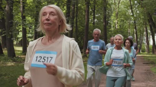 Aged Caucasian Woman Running in Park with Teammates