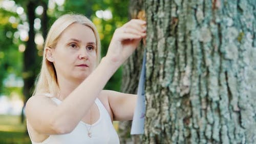 Young Woman Attaches an Ad To a Tree in the Park