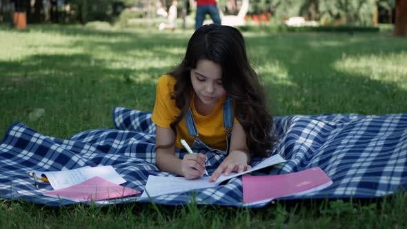 Thumbnail for Little girl lying on a blanket. Cheerful girl lying down teaches lessons outdoors