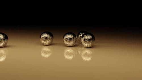 Mechanical Collision Of Golden Balls On A Glossy Surface.