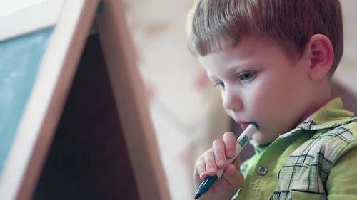 Little Boy in Green Shirt Holds Colorful Felt-tip Pen
