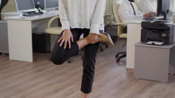 Cover Image for Caucasian Businesswoman Stretching Her Legs in Office