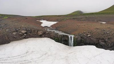 Waterfall and Snow in Mountains