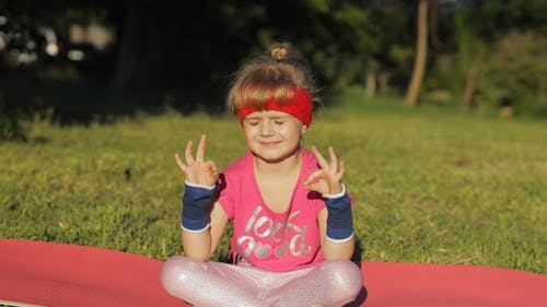 Child Sitting on Mat and Performing Yoga Meditation Outdoors in Park, Girl Doing Yoga Exercises