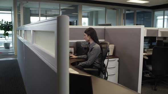 Panning view of woman in cubicle working on computer.